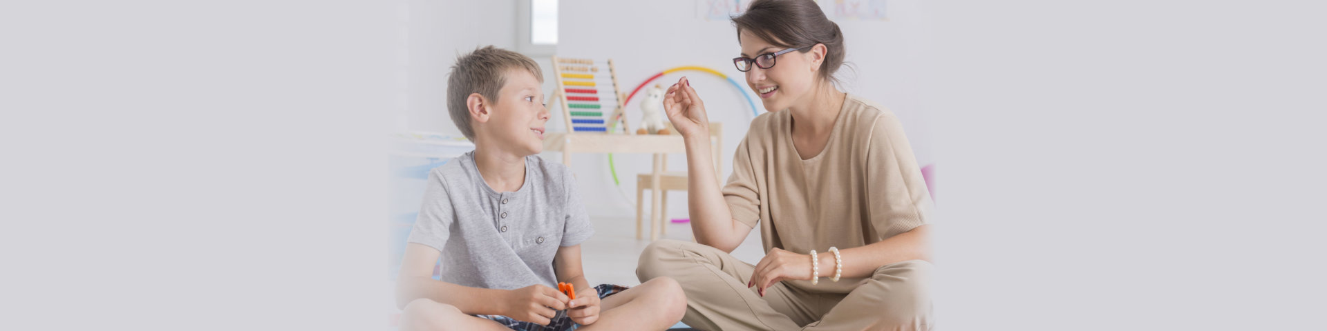 Young child and friendly teacher during play therapy session in bright office room, boy during speech and language therapy